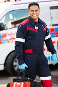 stock photo of paramedic  - handsome young paramedic carrying portable equipment - JPG