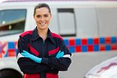 beautiful female paramedic with arms crossed in front of ambulance