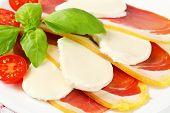 Sliced prosciutto crudo and mozzarella with fresh basil and tomatoes