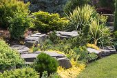 picture of garden sculpture  - Naturally sculptured flat top rocks from northwest Oregon are placed in a beautifully landscaped backyard among a variety of perennial evergreens and shrubs - JPG