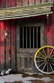 stock photo of wagon wheel  - Detail of old wagon wheel next to a wooden wild west typical house - JPG