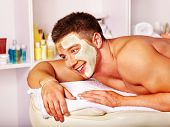 Man with clay facial mask in beauty spa.