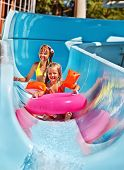 Children  on water slide at aquapark. Summer holiday.