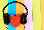 Headphones and hearts on wooden background