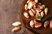Tasty brasil nuts on salver, on wooden background