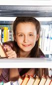 Smiling girl portrait through bookshelf