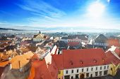 stock photo of sibiu  - Red roofs top view and shining sun in Sibiu - JPG