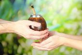 stock photo of calabash  - Man hands giving calabash and bombilla with yerba mate - JPG