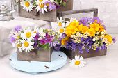 foto of kerosene lamp  - Beautiful flowers in crates with kerosene lamp on wooden stand on light background - JPG