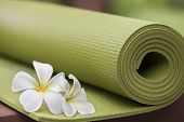 stock photo of yoga  - A green yoga mat with beautiful flowers
