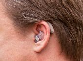 Close-up of a human ear with hearing aids