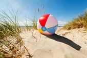 Beach ball resting in sand dune concept for childhood summer vacations, family holiday and healthy l