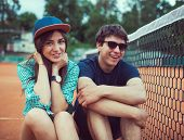 Young Couple Sitting On A Skateboard On The Tennis Court