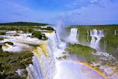 The roaring waterfalls in South America - Iguazu. Blanker jet fall between green jungle. Magnificent rainbow shines in the mist