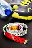 Sport shoes, measuring tape and water on grey background