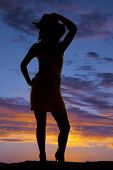 Silhouette Of Cowgirl With Hand On Hat And Hip