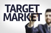 Business man pointing to black board with text: Target Market