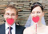 Happy Wedding Couple With Decorative Cardboard Hearts