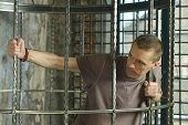 Man in cage with hands