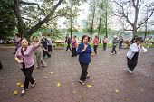 HANOI, VIETNAM - APRIL 6, 2014: Group of Vietnamese seniors practice Tai Chi early in the morning on the bank of Hoan Kiem lake on April 6, 2014 in Hanoi.