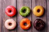 Delicious donuts with glaze on wooden background