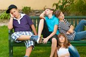 pic of boring  - Bored teenagers sitting and lying on the bench on beautiful spring day - JPG