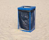 picture of dustbin  - Metal blue garbage dustbin on beach sand in sunny day - JPG