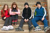 Group of happy teenagers having fun in roller skates