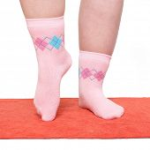 Overweight woman in funny socks excercising on red carpet.