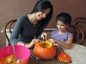Young Woman Carving A Halloween Pumpkin With Her Seven Year Old Daughter