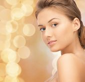 beauty, people and health concept - beautiful young woman with bare shoulders over beige lights background