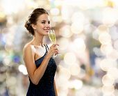 party, drinks, holidays, luxury and celebration concept - smiling woman in evening dress with glass of sparkling wine over lights background