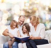 family, childhood, holidays and people - smiling mother, father and little girls reading book over lights background