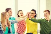 education and happiness concept - smiling students at school making high five gesture