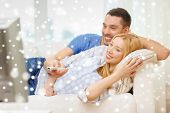 love, family, technology, entertainment and people concept - smiling couple watching tv and lying on sofa at home