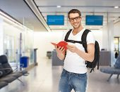 travel, education, tourism and people - smiling student with backpack and book at airport