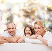 family, childhood, holidays and people - smiling mother, father and little girl over lights background