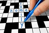 Hand filling in a crossword - family and home