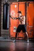 image of pugilistic  - Young man boxing workout in an old building - JPG