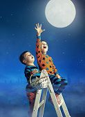 stock photo of reach the stars  - Two young boys reaching stars - JPG