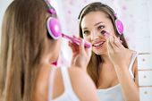 Teen girl in bathroom makeup and listening to music