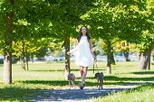 pic of greyhounds  - Young attractive girl dressed elegantly walking with two greyhounds in the park - JPG