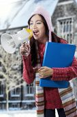 Girl Shouting With Megaphone Near School Building