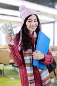 Schoolgirl In Knitted Sweater Holds Money