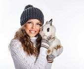Girl In Knitted Hat And Sweater Holding Rabbit