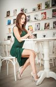 pic of redhead  - Fashionable attractive young woman in green dress sitting in restaurant. Beautiful redhead posing in elegant scenery with an orange juice glass on the table. Pretty female relaxing, indoor shot.