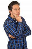 image of flirty  - handsome young happy flirty latin man wearing a blue plaid shirt posing with hand on cheek isolated on white - JPG