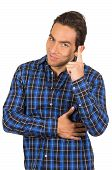 young handsome man wearing a blue plaid shirt posing with finger pointing up
