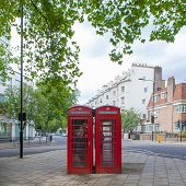 Two typical red phone booths in a London street