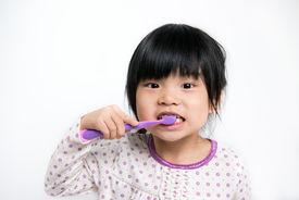 image of pyjama  - Little Asian girl in pyjamas brushing teeth - JPG